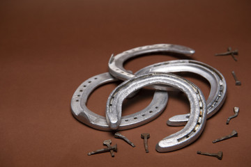 Pile of horseshoes and nails isolated on a brown background