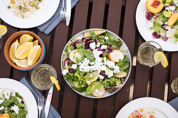 Above view background image of delicious light meal on wooden table: salads and fruits in elegant bowls surrounded by glasses with refreshing lemonade