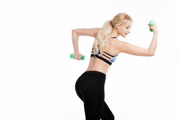 Fit young pretty woman exercises with dumbells. Biceps exercise. Health conception.