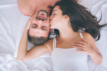 Beautiful man and woman are lying in white bed. Guy keeps eyes closed and smiles. Girl is touching his cheek and kissing. They are happy.