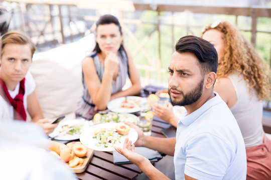Portrait of frowning Middle-Eastern man complaining about food during lunch with friends in cafe, copy space
