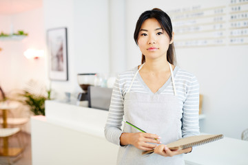 Pretty young Asian waitress in apron ready to serve new clients of cafe