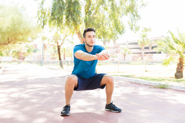 Man Performing Squats Before Jogging On Footpath In Park