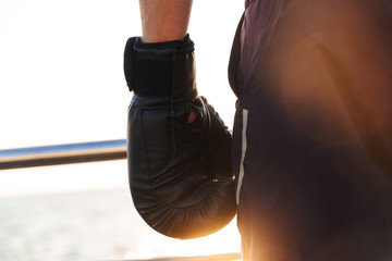 Cropped image of Sportsman in boxing gloves standing on beach