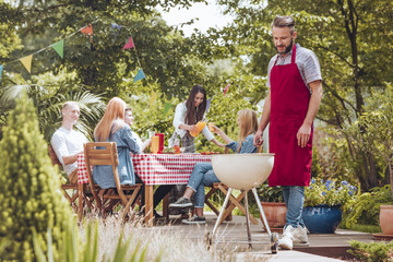 A young man wearing a burgundy apron cooking on a white grill. People sitting around a table and having fun during a celebration in the backyard.