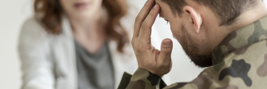 Close-up of a sad soldier with PTSD talking about his fears with a psychiatrist sitting in blurred background