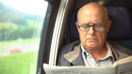 Model Released - Commuter reading newspaper in train on way to work