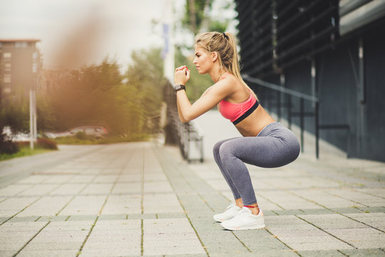 Women exercise squats. Side view.