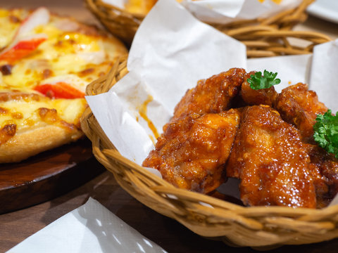 Deep fried chicken in a basket with parsley and seafood pizza topping with Crab, shrimp and ham On a wooden tray