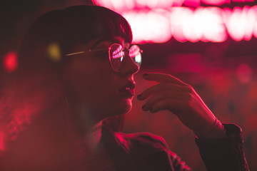 Young redhead dancer with glasses on neon lights