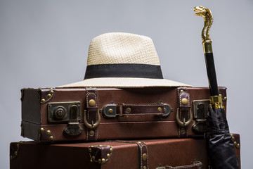 Old suitcase, hat and umbrella. Vintage travel set.