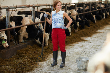 Full length portrait of modern young woman smiling happily while cleaning barn or cow shed, copy space