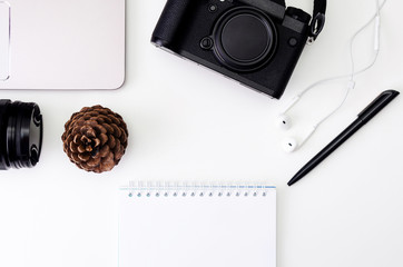 desk workspace with laptop keyboard, hipster camera, lens, notepad for writing with black pen on white background. flat lay, top view. Vintage retro photo style.