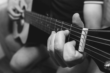 Man at home is playing the guitar. Guys hands are taking the chord on strings. Music making lifestyle concept. Free time hobby for everyone. Retro black and white guitar photo.