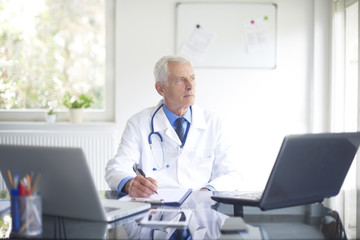 Senior male doctor working at desk in the specialist office