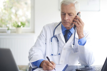 Portrait of male doctor making call with his patient and writing down the diagnosis while sitting at consulting room.