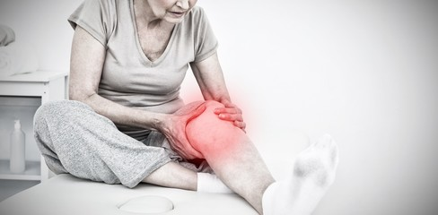 Composite image of senior woman with her hands on a painful knee