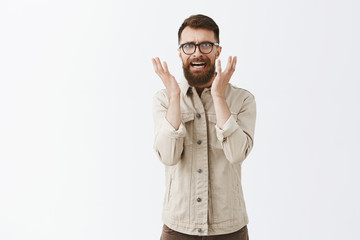 Pissed disstressed and annoyed adult hipster guy with long beard in black trendy glasses and beige jacket frowning raising palms in anger hearing nonsense and being mad with stupid conversation