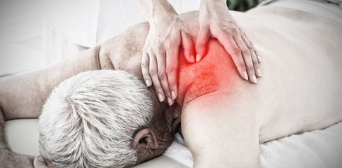 Composite image of therapist massaging back of senior man