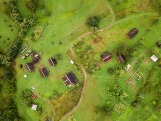 arial veiw of rural road, green field, trees and buildings. drone shot