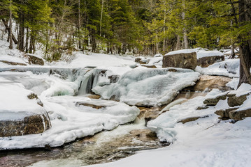 Frozen water fall rapids in winter time with snow