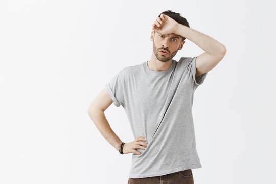 Man feeling relieved escaping from dangerous situation whiping sweat from forehead breathing out and gazing down with tired and exhausted expression holding hand on waist over gray wall