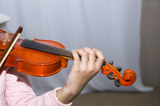 A hand dark skinned little girl using a violin while playing