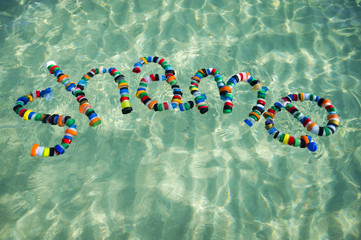 Colorful bottle caps spell out the word 'shame' on the sea. Take action on pollution - reduce, reuse and recycle