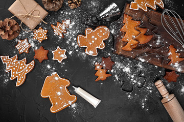 Woman decorating gingerbread Christmas cookies with icing sugar. Christmas preparations concept. Top view with copy space.