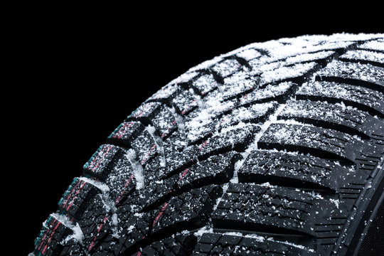 Winter car tires with snow wheel profile structure on black background - Close up