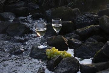 Weißwein und Weintrauben auf Steinen im fließenden Wasser bei Morgensonne.