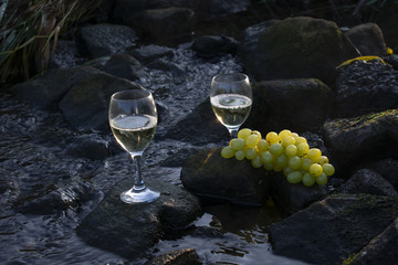 Weißwein und Weintrauben auf Steinen im fließenden Gewässer bei Sonnenaufgang.