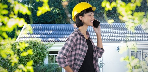 Composite image of female architect talking on mobile phone