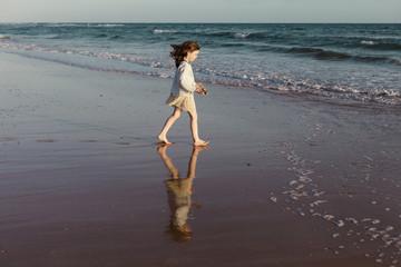 Girl on beach walking towards ocean, Spain