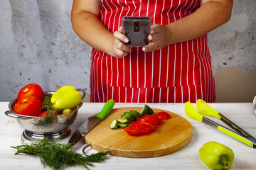 Woman in a red apron takes pictures of food