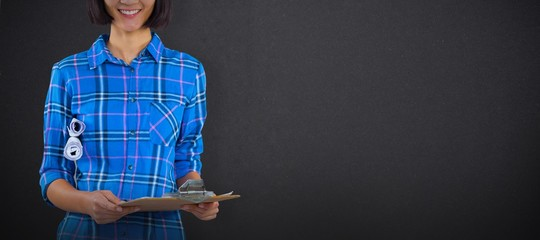 Composite image of female architect holding clipboard and