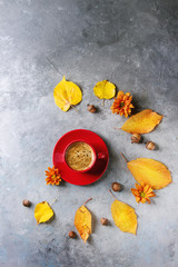 Red cup of black coffee with foam decorated by yellow autumn leaves, aster flowers and acorns over grey texture background. Flat lay, space. Seasonal background.