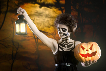 Witch with sugar skull makeup holding pumpkin at scary forest background. Copy space