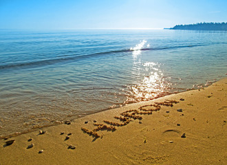 Sandy beach at Lake Huron in Northern Michigan and drawn word. Beautiful view of text on sand and brilliant glare of bright sunbeams on blue surface lake water.