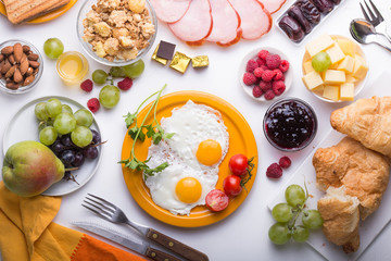 Homemade breakfast with sunny side up fried egg croissant toast coffee fruits vegetable  and orange juice in top view with copy space. American breakfast on breakfast table.