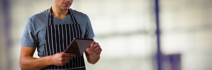 Composite image of male waiter using digital tablet