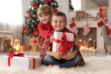Cute little children with Christmas gift boxes at home