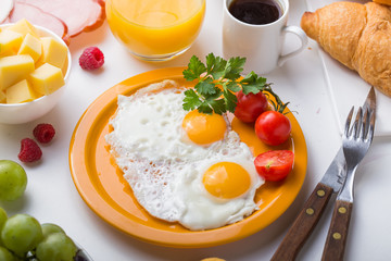 Homemade breakfast with sunny side up ceral egg toast coffee fruits coffee croissants and orange juice in top view with copy space. Delicious homemade american breakfast concept for background.