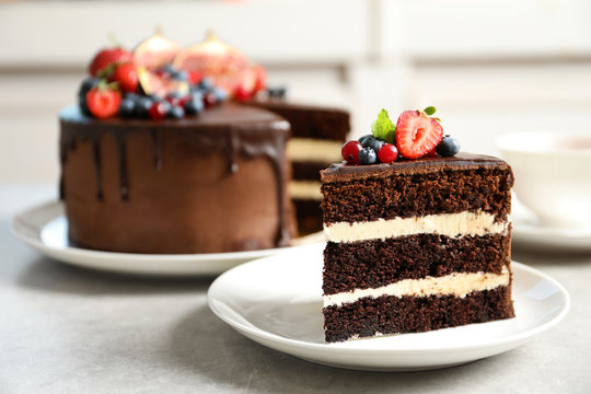 Plate with slice of chocolate sponge berry cake on grey table