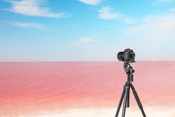 Professional camera on tripod near pink lake
