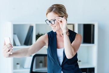 smiling businesswoman in eyeglasses taking selfie on smartphone in office