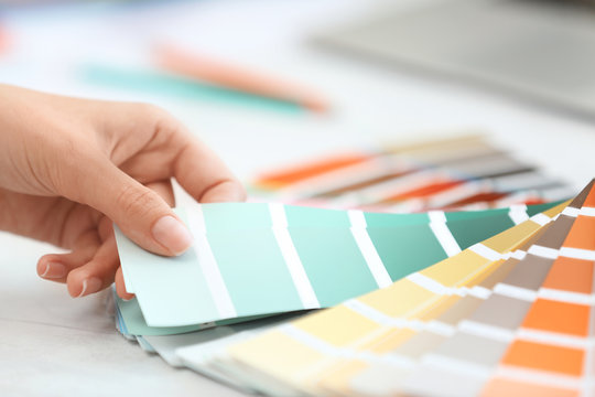 Woman with paint color palette samples at table, closeup