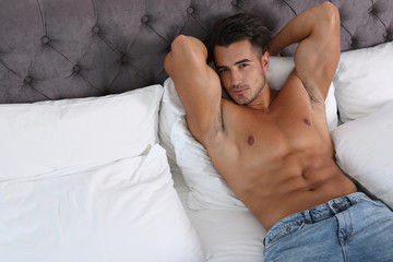 Sexy young man lying on bed with soft pillows at home