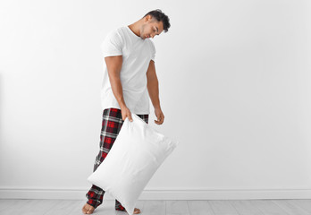 Sleepy young man with soft pillow near white wall