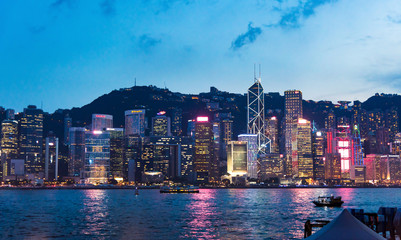 Foto auf Acrylglas Hongkong Hong Kong cityscape view of modern buildings over water from Victoria harbor at blue hour